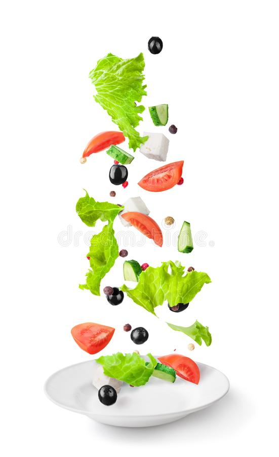 Sliced vegetables and salad ingredients falling in white ceramic plate isolated. On a white background royalty free stock photography
