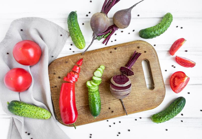 Sliced vegetables for salad on wooden cutting board, surrounded by vegetables. Flat lay, top view stock photo