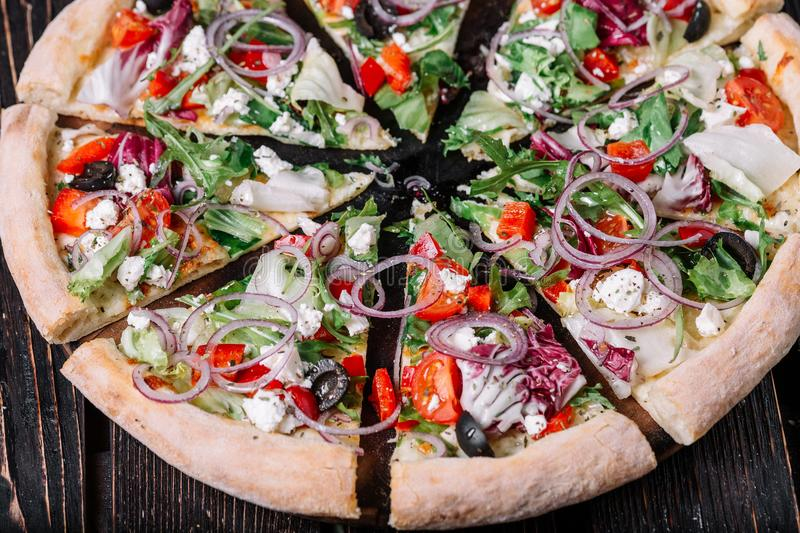 Sliced vegeterian pizza on wood background. Sliced vegeterian pizza on dark wood background royalty free stock photos