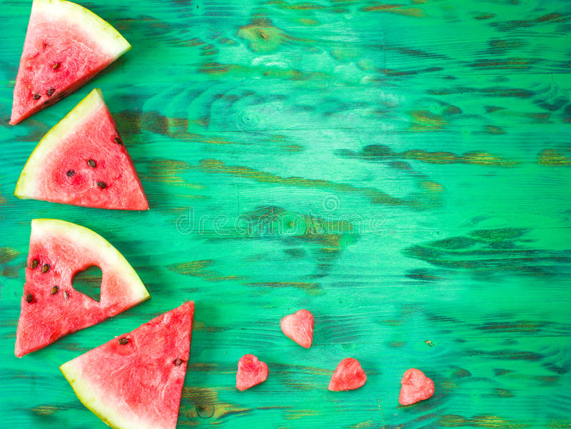 Sliced watermelon on wooden background. Sliced watermelon on green wooden background withspace for text. texture stock images