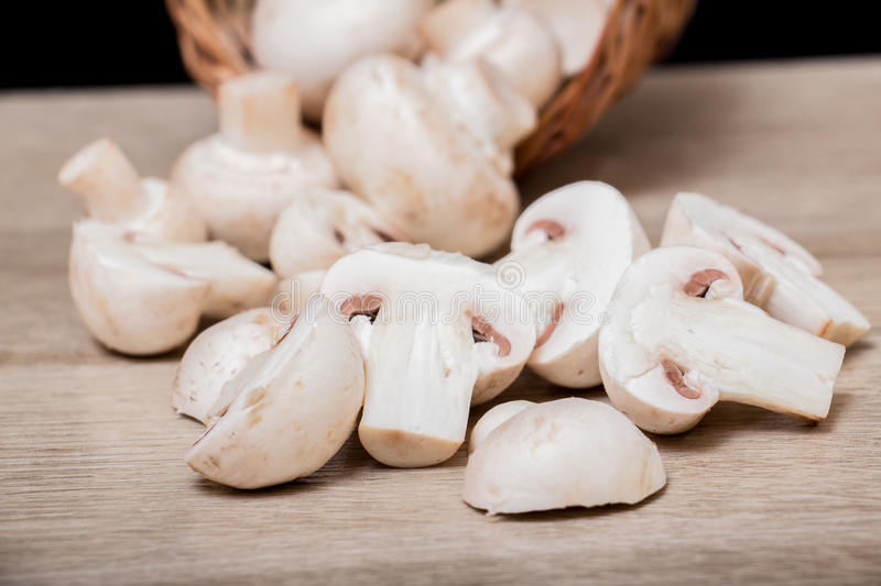 Sliced White Mushrooms. Close up of fresh sliced white mushrooms on wooden stock photos