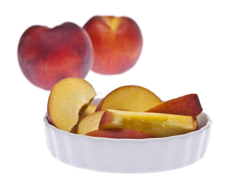 Sliced and Whole Fresh Peaches. With the Focus on the Sliced Peaches Isolated on White with a Clipping Path stock photo