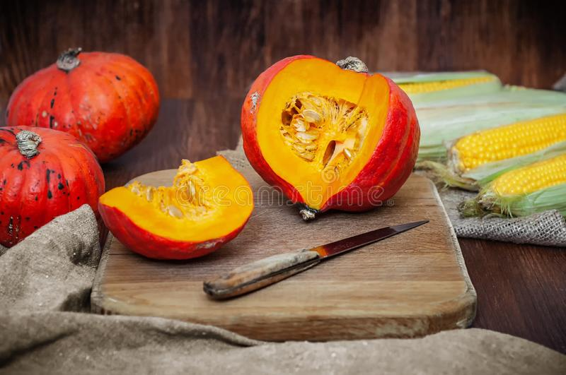 Sliced and whole pumpkins, corn on cutting board with knife on wooden background with canvas fabric. Side view still royalty free stock photo