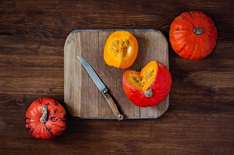 Sliced and whole pumpkins on cutting board with knife on wooden background. Top view in rustic style. Flatlay royalty free stock photography