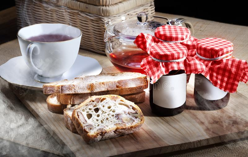 Sliced whole wheat bread with fruit jam in a bottle, accompanied by a cup of tea with a clear glass pot. Served on unique fibrous royalty free stock image