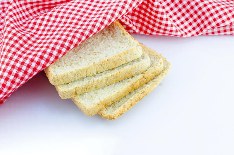Sliced wholewheat bread and napkin on white background stock photography