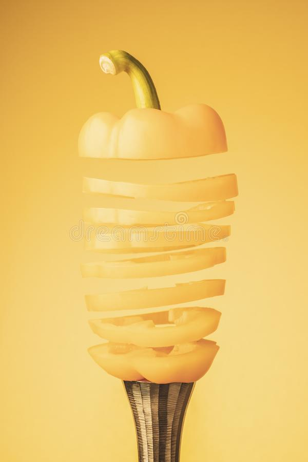 Sliced yellow bell pepper lies on top of a steel candlestick. Sliced yellow colored peppers lies on top of a steel candlestick against a yellow background stock photos