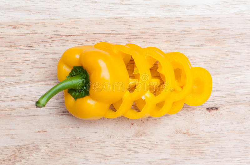 Sliced Yellow bell peppers on wooden cutting board stock images