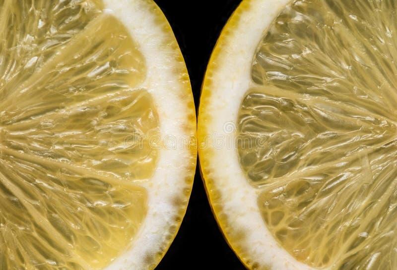 Sliced yellow lemon on black background closeup. Food background. Flat lay. Juicy ripe fresh citrus fruit lemon. Top. Sliced yellow lemon on black background stock photo