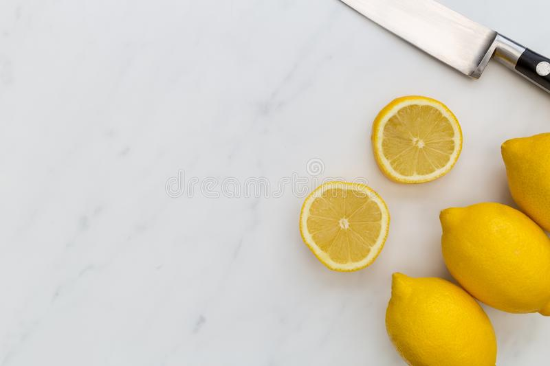 Sliced lemon fruits and knife on white marble background with co. Sliced yellow lemon fruits and knife on white marble background with copy space stock photography