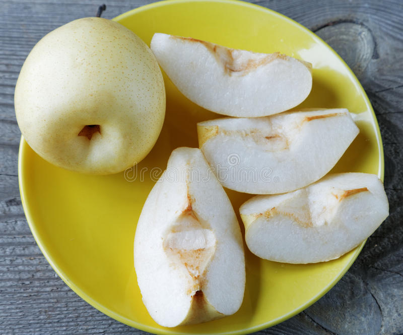 Sliced yellow pear in a bowl on a table stock image