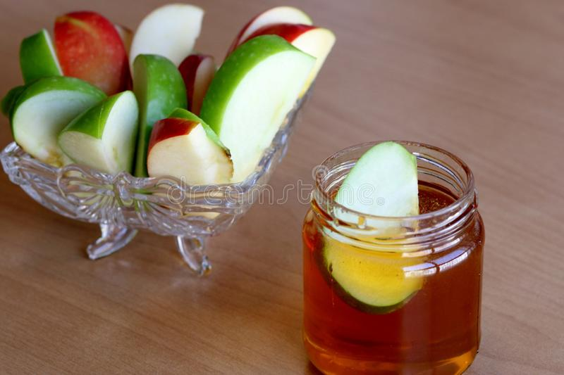Slices of apples and a jar of honey stock photography