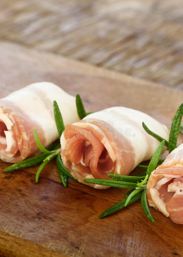 Slices of bacon. Slices of rolled bacon with rosemary royalty free stock photos