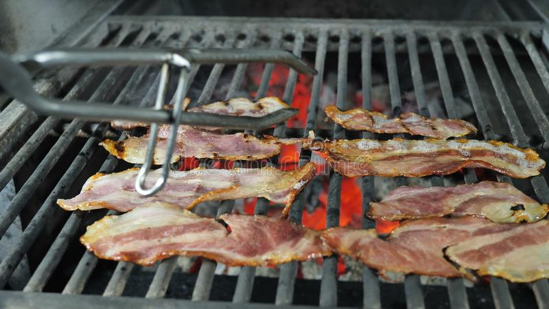 Slices of bacon are grilled, the fat from the bacon drains from the fried bacon, the chef in black gloves with iron royalty free stock photography