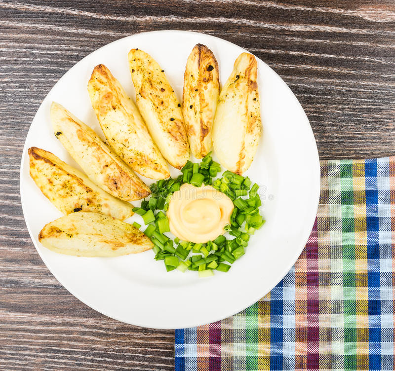 Slices of baked potatoes with mayonnaise and leek, checkered nap. Kin on black wooden table royalty free stock images