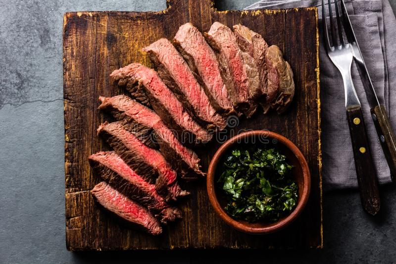Slices of beef medium rare steak on wooden board, glass of red wine. On slate background royalty free stock photography