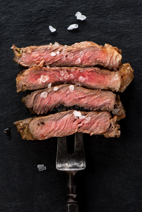 Slices beef Steak Ribeye on meat fork stock photography