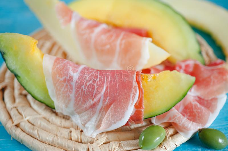 Slices of cantaloupe melon, ham and olives stock image