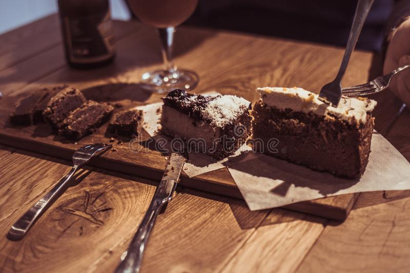 Slices of carrot cake cheese cake brownie with forks stock photography