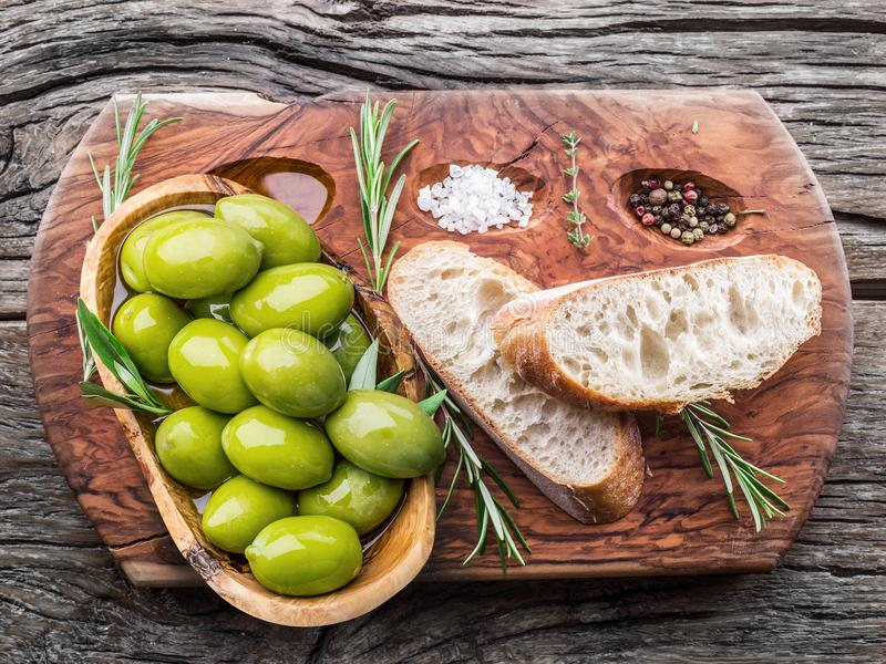 Slices of ciabatta with olives and spices on the serving wooden stock images