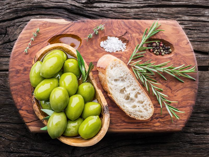 Slices of ciabatta with olives and spices on the serving wooden stock photos