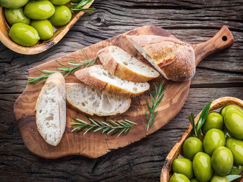 Slices of ciabatta with olives and spices on the serving wooden royalty free stock photos