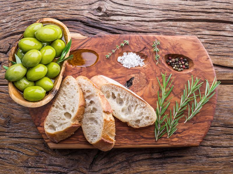Slices of ciabatta with olives and spices on the serving wooden stock photo