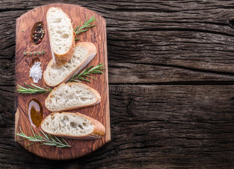 Slices of ciabatta with rosemary herb on the serving wooden tray royalty free stock image
