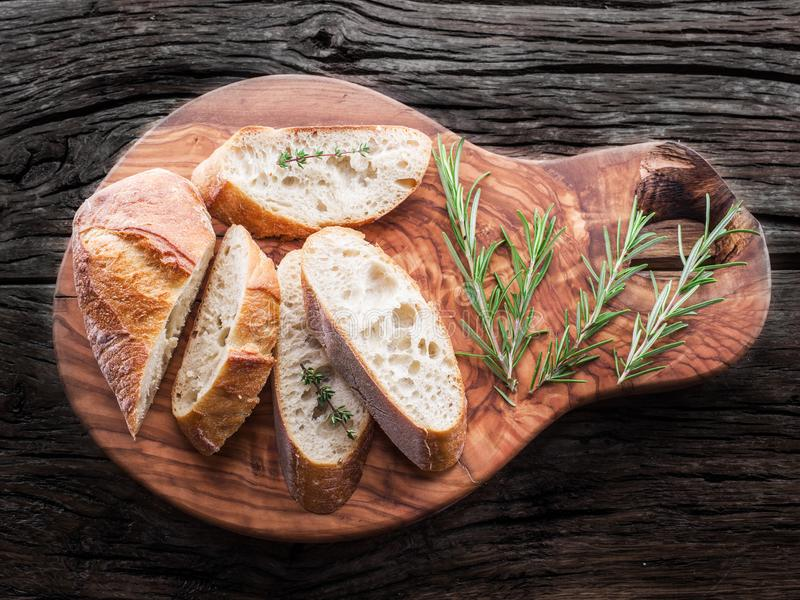 Slices of ciabatta with rosemary herb on the serving wooden tray stock photography
