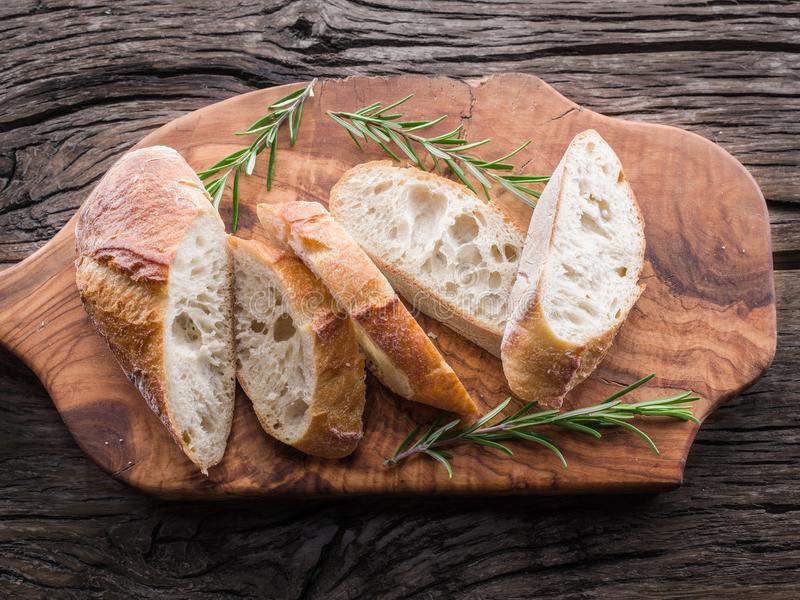 Slices of ciabatta with rosemary herb on the serving wooden tray royalty free stock photo