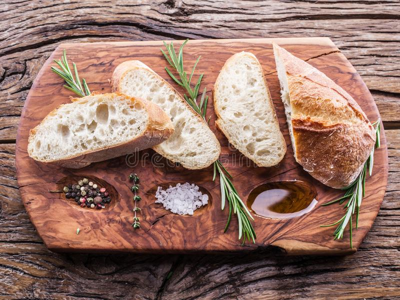 Slices of ciabatta with rosemary herb on the serving wooden tray royalty free stock photography