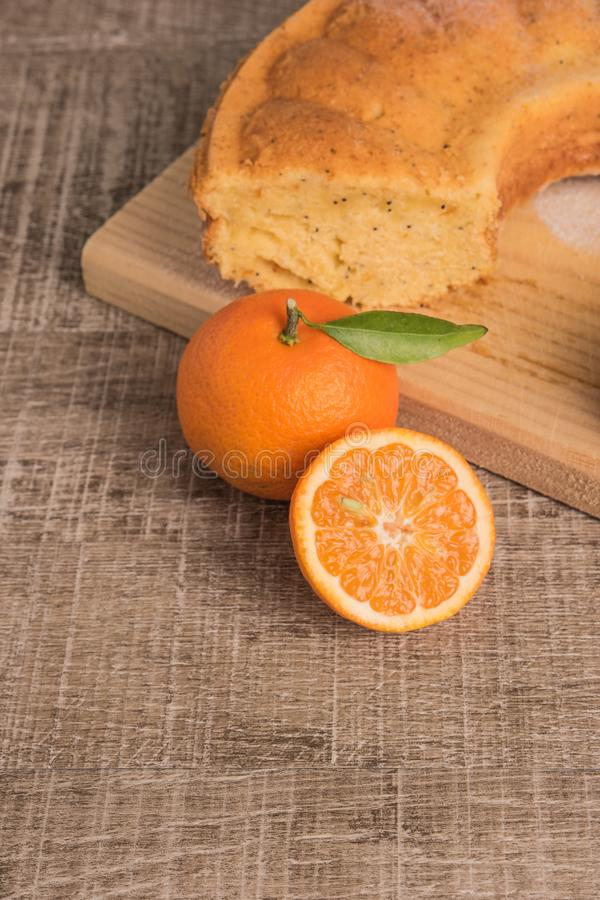 Slices of clementine cake with powdered sugar topping. Cake on a board with fresh clementines on wooden board royalty free stock photos