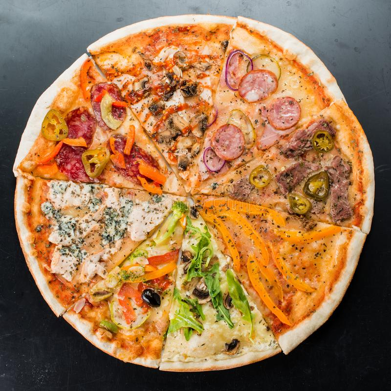 Slices of different pizzas collected in one pizza on a dark back stock image