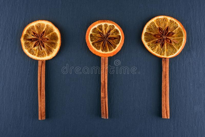 Slices of dried orange with star anise and cinnamon spice on dark background. Spices are lined in the form of flowers. stock image