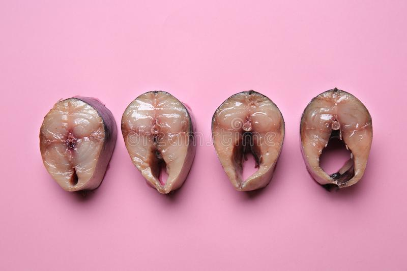 Slices of fish on color background. Erotic concept stock photography