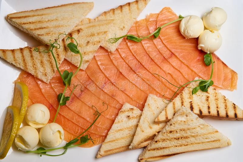 Slices of fish with toast and butter on a white dish. Slices of fish with toast and butter on white dish royalty free stock photo