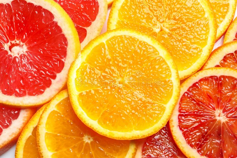 Slices of fresh citrus fruits as background. Top view stock photos