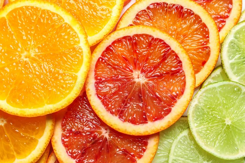 Slices of fresh citrus fruits as background. Top view royalty free stock photo