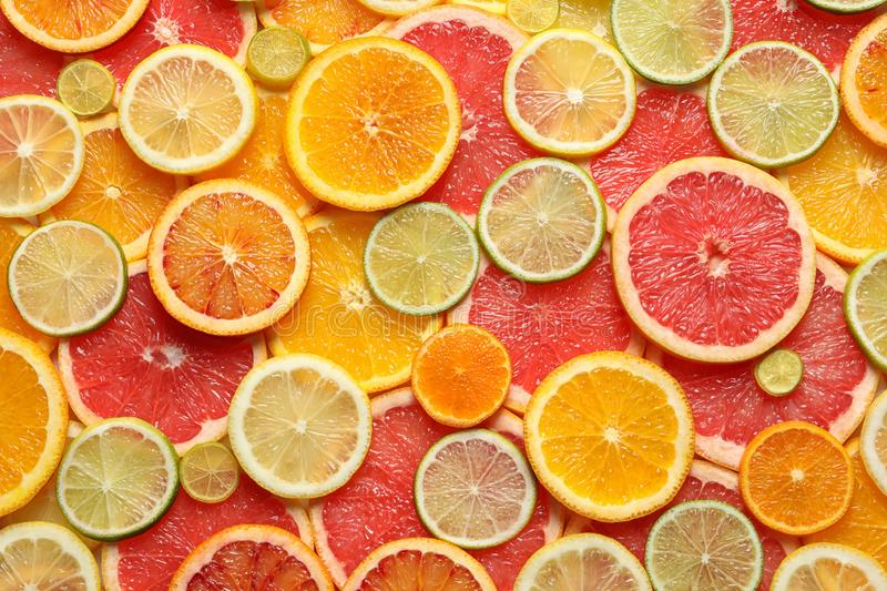 Slices of fresh citrus fruits as background. Top view stock images