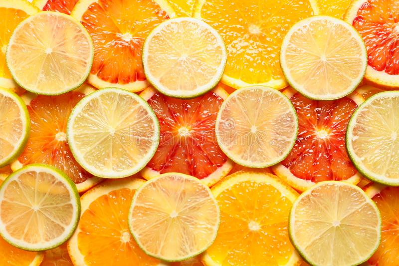 Slices of fresh citrus fruits as background. Top view stock photography