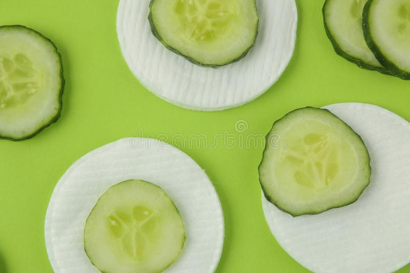 Slices of fresh cucumber and cotton sponge on a bright green background. cucumber cosmetics concept. skin care. tonic cucumber ext. Ract stock photography