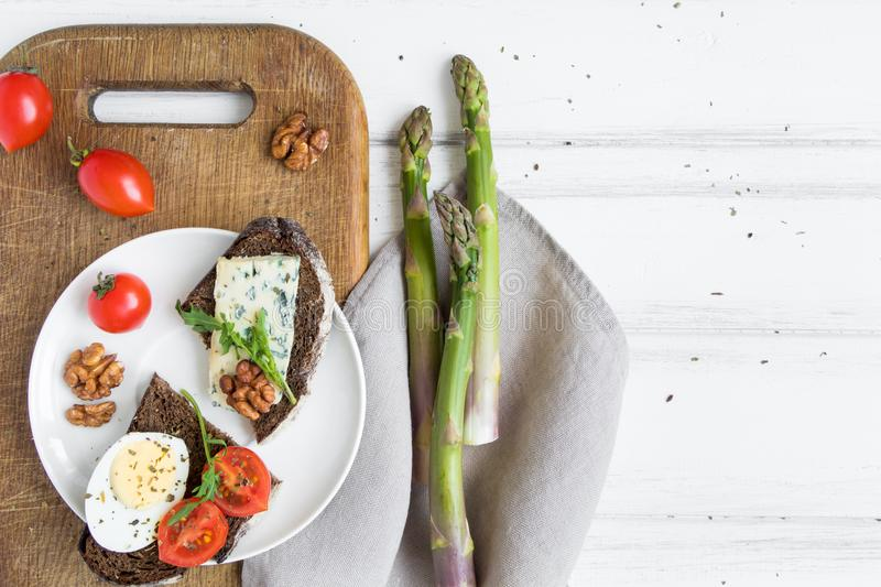 Slices of dark bread with blue cheese, eggs, tomatoes on wooden cutting board decorated with asparagus. Flat lay, top view royalty free stock photos