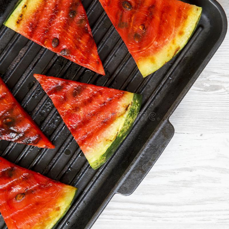 Slices of fresh grilled watermelon in grilling pan on a white wooden surface, top view. Healthy organic summer fruit. Close-up stock image
