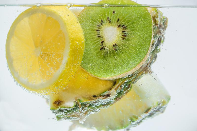 Slices of fresh pineapple, lemon and kiwi in clear clear water. royalty free stock images