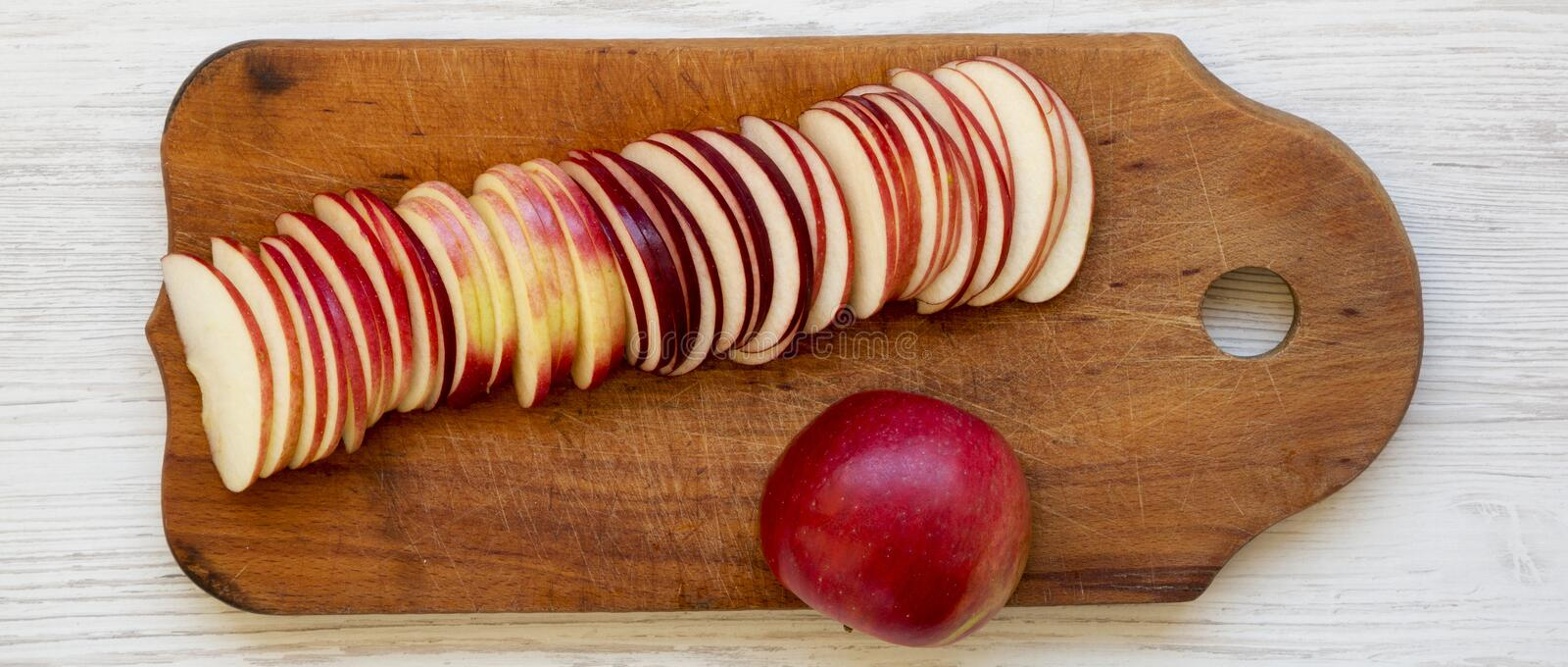 Slices of fresh red apples on rustic wooden board over white wooden background, top view. Flat lay, overhead, from above. Close-up royalty free stock photos
