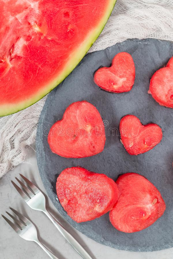 Slices of fresh seedless watermelon cut into heart shape on slate board, flat lay, vertical. Slices of fresh seedless watermelon cut into heart shape on a slate royalty free stock photo
