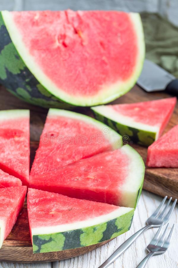Slices of fresh seedless watermelon cut into triangle shape on wooden plate, vertical stock image