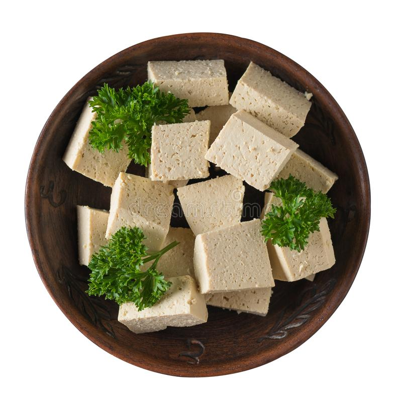 Slices of fresh tofu cheese in a clay bowl isolated on a white background. Soy cheese. Flat lay. royalty free stock images