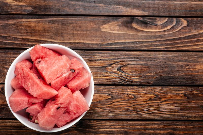 Slices of fresh watermelon on plate over wood background royalty free stock image