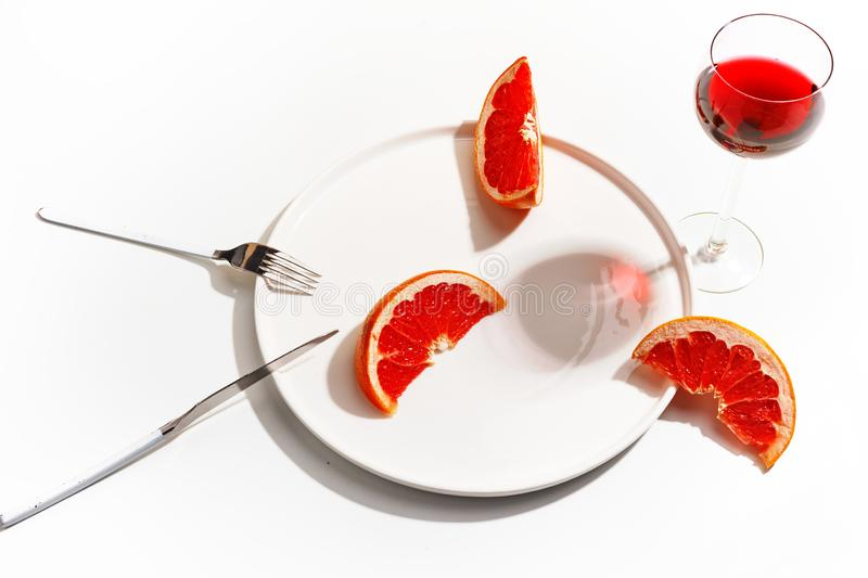 Slices of grapefruit on a white plate. Minimalistic concept. Top view.  royalty free stock image